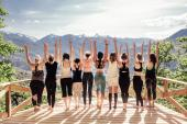 Rear view of group of joyful happy athletic young women in gymnastic clothes raise their hands up and enjoy joint activities in open air among mountains. Concept of sports and personal achievements